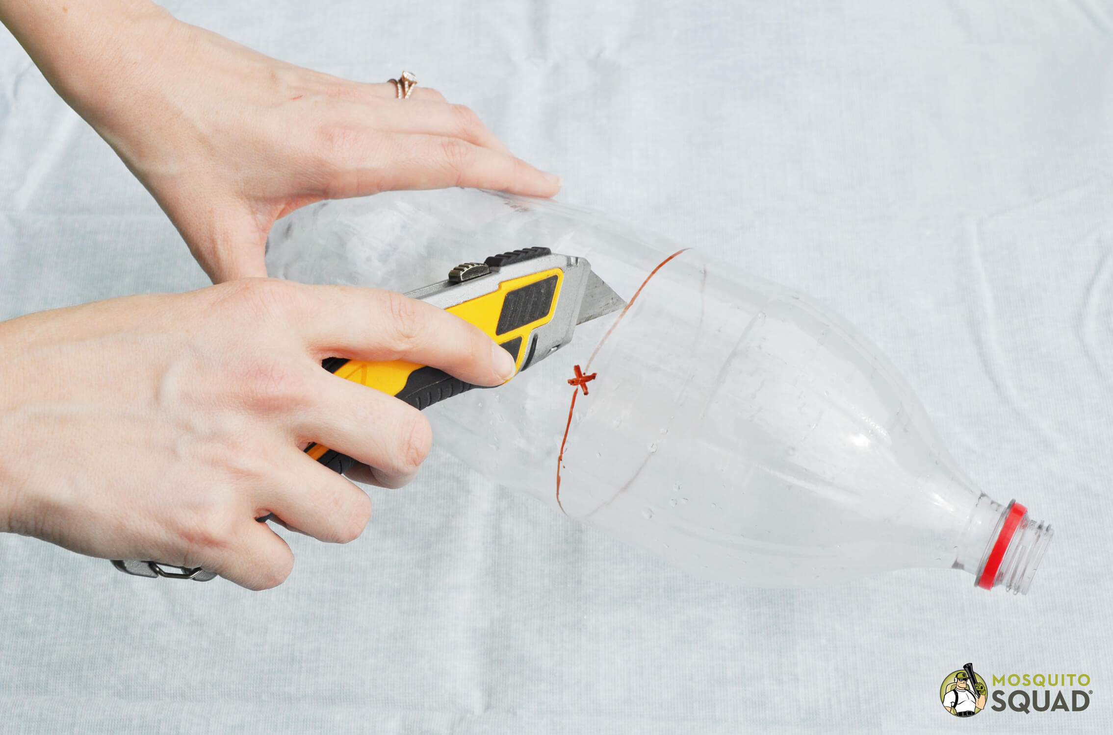 hand cutting a plastic bottle in half with box cutters