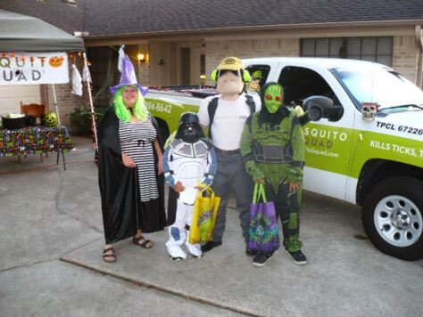 A family in Halloween costumers (including a Dread Skeeter costume) poses in front of a Mosquito Squad truck